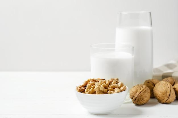 호두와 견과류 흰색 나무 배경에서 우유. 식물성 단백질, 비타민 및 유용한 아미노산이 포함 된 제품입니다. 공간을 복사하십시오.