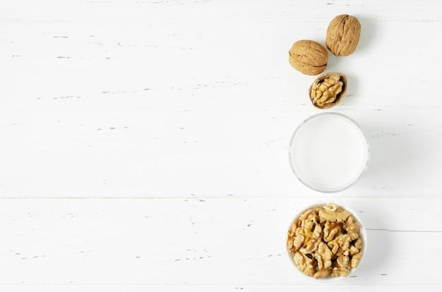 흰색 나무 바탕에 호두와 견과류로 만든 우유. 식물성 단백질, 비타민, 유용한 아미노산을 함유한 제품. 공간을 복사합니다.
