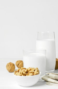 흰색 나무 바탕에 호두와 견과류로 만든 우유. 식물성 단백질, 비타민, 유용한 아미노산을 함유한 제품. 건강하고 채식주의 식단을 위해. 공간을 복사합니다.