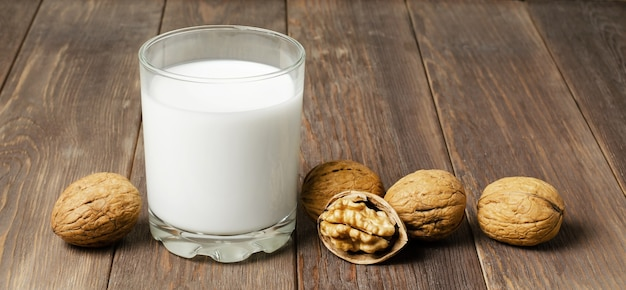 Milk from walnuts and nuts on a brown wooden background. products containing vegetable protein, vitamins, and useful amino acids. copy space