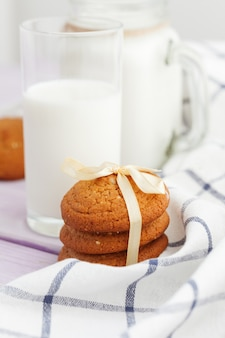 Milk glass and biscuit cookies with kitchen cloth on light background