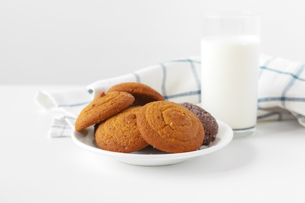 Milk glass and biscuit cookies with kitchen cloth on light