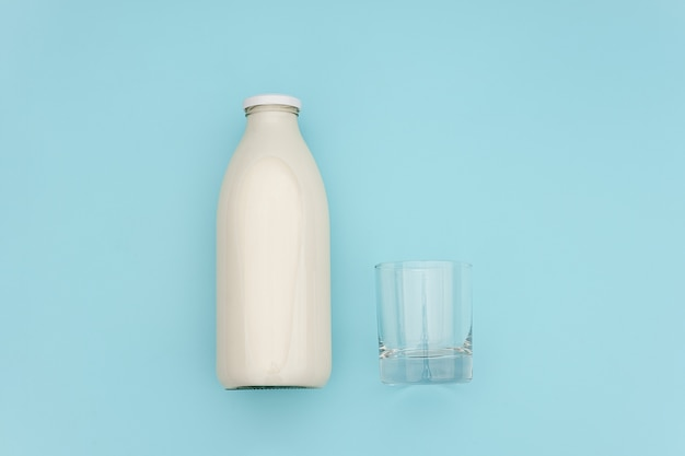 Milk in glass bottle and empty glass on blue
