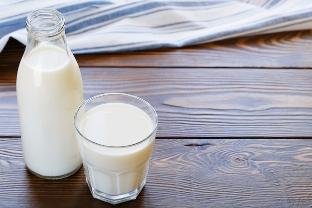 Milk in glass bottle and glass on wooden table.