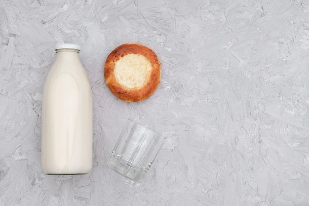Milk in glass bottle, one empty glass and freshly baked bun on gray