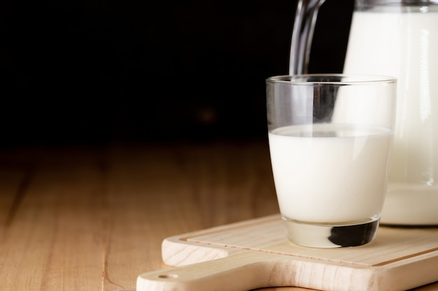 Milk in glass and jug on wooden table