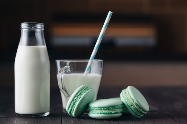 Milk glass with cookies on rustic wooden table with copy space