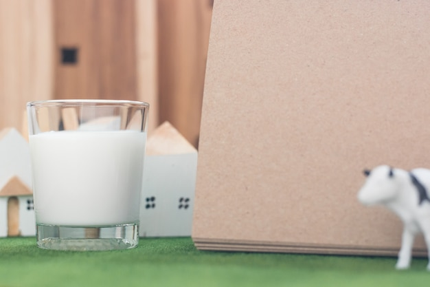 Milk in glass with empty paper note on simulation grass