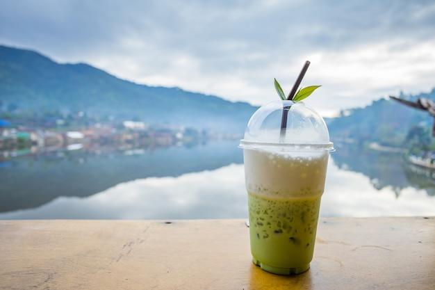 Milk green tea on the table riverside view at rak thai village, mae hong son, thailand