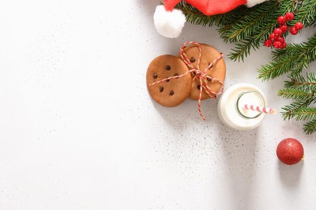 Milk, homemade gingerbread cookies, santa hat on white background