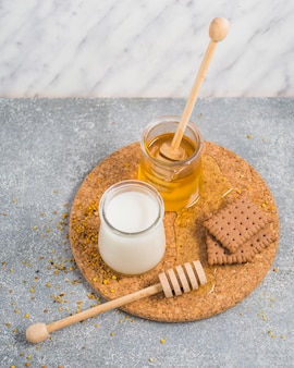 Milk and honey pot with baked biscuits and honey dipper on cork coaster