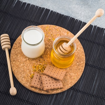 Milk and honey pots with biscuits and bee pollens on cork coaster