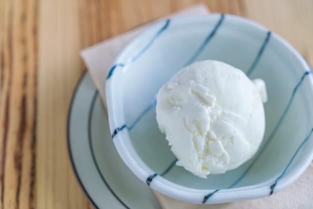 Milk ice cream in bowl on wood table .