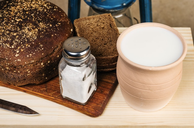 항아리에 담긴 우유, 빵, 도마에 소금. 소박한 스타일의 정물