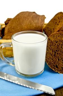 籐のバスケットにライ麦パンと青いナプキンのナイフと白い背景で隔離の木の板とガラスのゴブレットのミルク