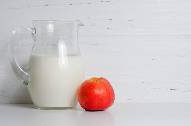 유리 용기와 사과에 우유. 자연과 건강 식품의 개념. 흰 배경. 공간 복사