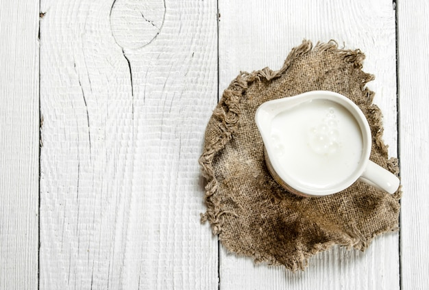袋の中のマグカップのミルク。白い木の背景に。