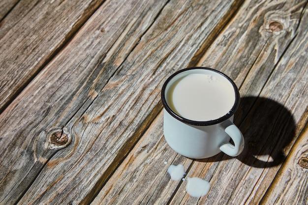 거친 나무 테이블에 에나멜을 입힌 밝은 파란색 머그잔에 우유. 아침 빛