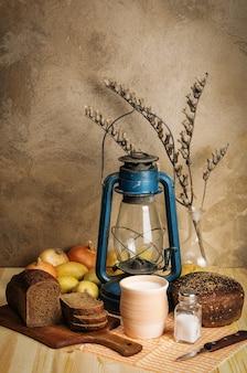 Молоко в керамической посуде ржаной хлеб соль овощи сухая ветка белены и керосиновый фонарь