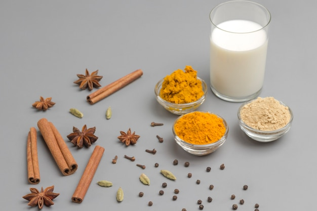 インドの飲み物ターメリック飲料を調理するための材料とガラスの牛乳