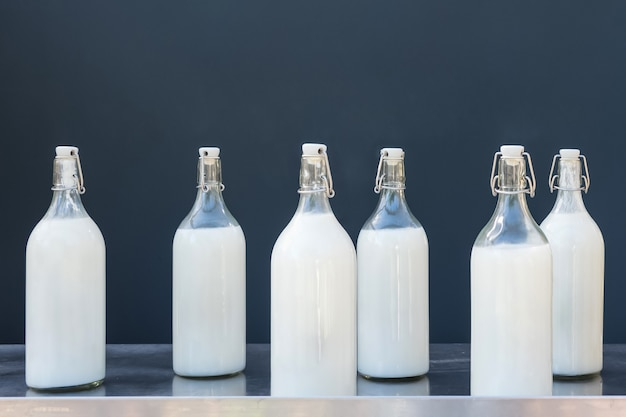 Молоко в больших стеклянных бутылках на сером.