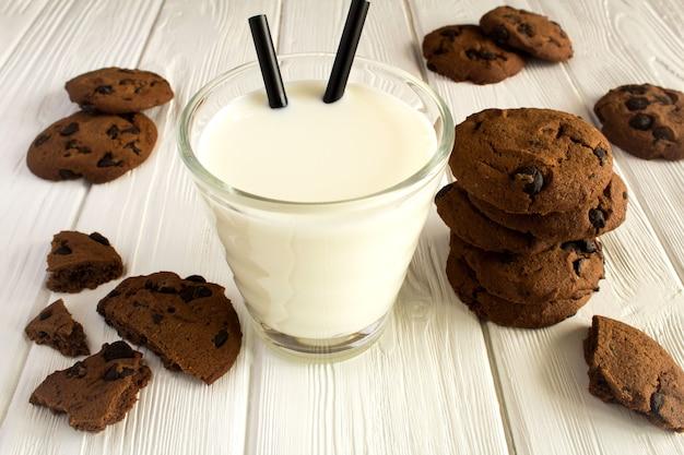 Молоко в стакане и шоколадное печенье на белой деревянной поверхности