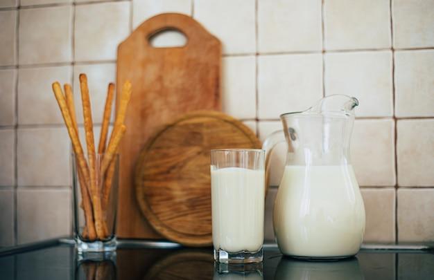Молоко в стакане стоит на столе на кухне дома