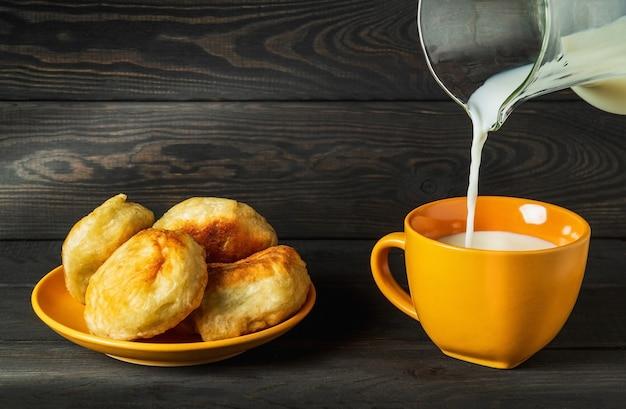 우유는 용기에서 노란색 머그잔에 부어집니다. 우유와 수제 도넛으로 맛있는 축제 아침 또는 저녁 식사를위한 아이디어