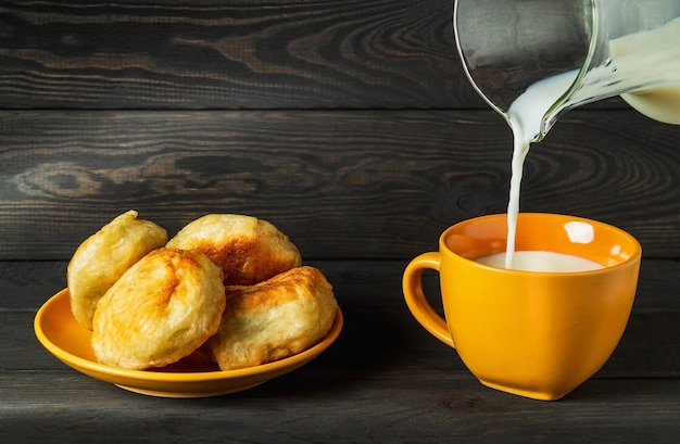 Milk is poured from a jug into an yellow mug. idea for a delicious festive breakfast or dinner with milk and homemade donuts
