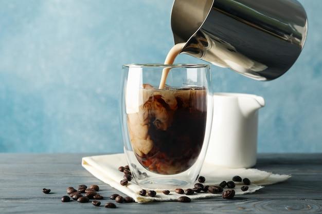 一杯のコーヒーに牛乳を注ぐ。アイスコーヒーと組成