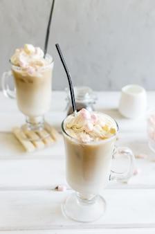 Молоко наливается в стакан с кубиками льда для кофе