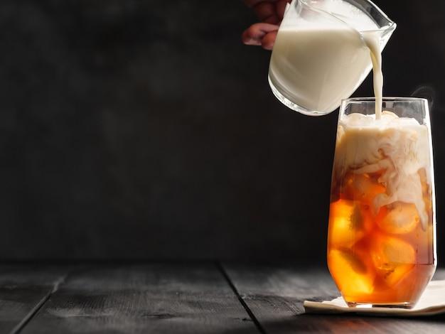 우유는 우유 용기의 회색 나무 테이블에 얼음과 커피가 담긴 하이볼 잔에 붓습니다. 우유와 얼음 커피. 회색 배경.