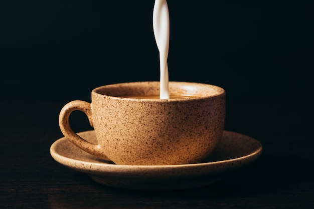 Milk is pouring into a cup of coffee.