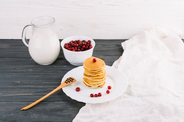 Milk jar; red currants berries and pancakes on wooden table