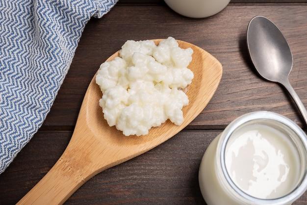 Milk kefir grains in spoon on wooden table