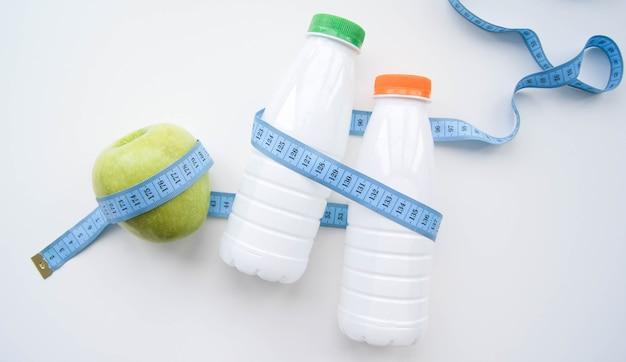 Молоко, кефир, йогурт или вода с измерительной или сантиметровой лентой на белом фоне
