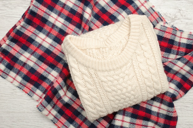 Milk knitted sweater on plaid. fashionable