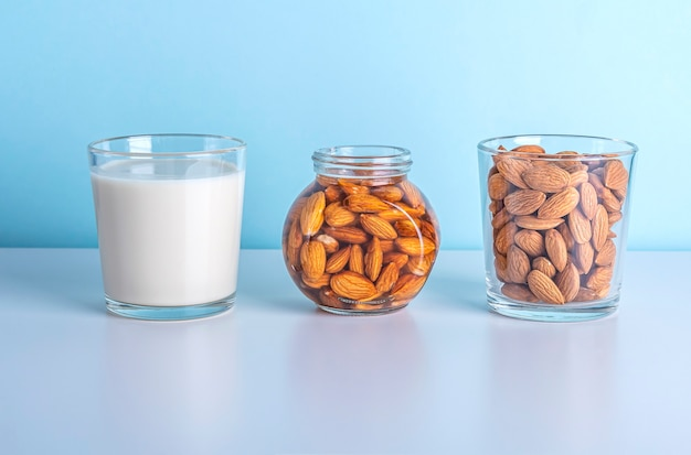 Milk and nuts on and a glass and a jar on blue background