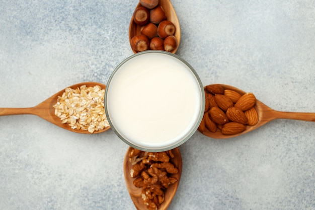 Milk and nuts in wooden spoons