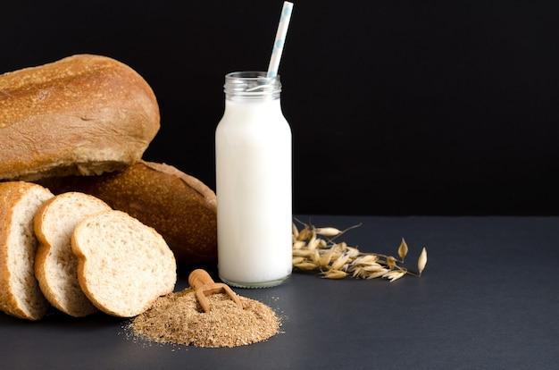 Молоко, овсяные отруби и ломтики хлеба на черном фоне