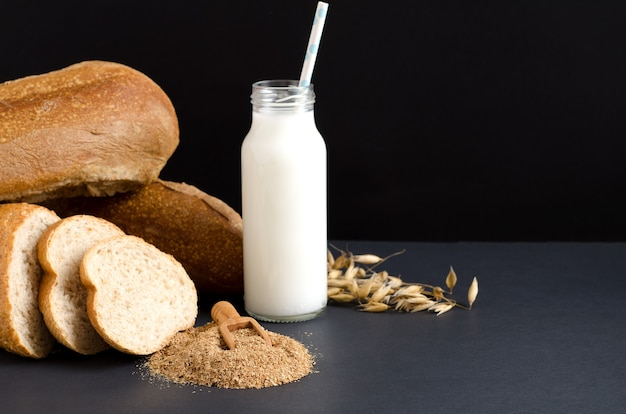 Milk, oat bran and bread slices on black background