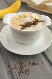 灰色の木製の背景の白いプレートに亜麻仁、バナナ、ココナッツチップスとミルクオートミール。閉じる。場所は垂直です。