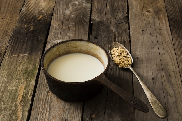 Milk in the old saucepan and spoon of oat over the rustic wooden background