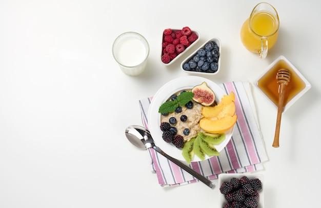 ミルク、オートミールのお粥とフルーツのプレート、透明なガラスのデカンターで絞りたてのジュース、白いテーブルのボウルに蜂蜜。健康的な朝食