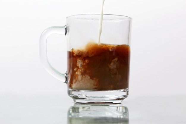 투명한 블랙 커피 컵에 우유를 부어