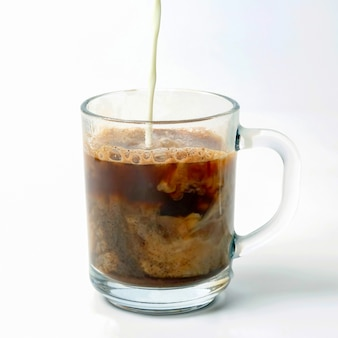 블랙 커피의 투명한 컵에 우유를 부어