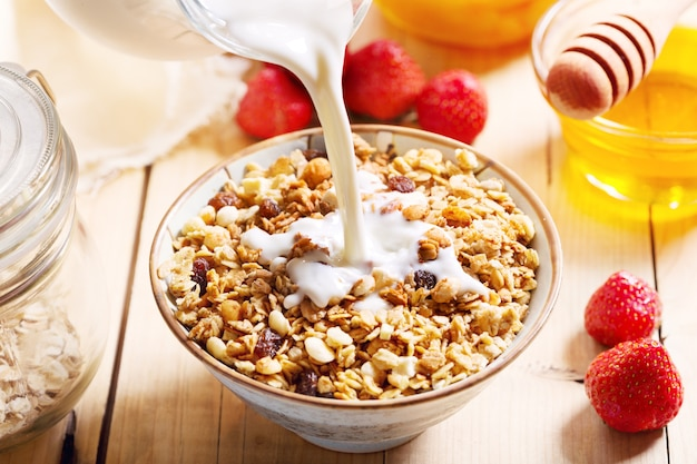 Milk pouring into bowl of muesli on wooden table