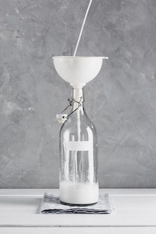 Milk pourred in bottle with funnel