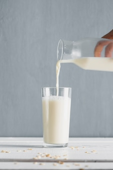 Milk pourred in glass with bottle