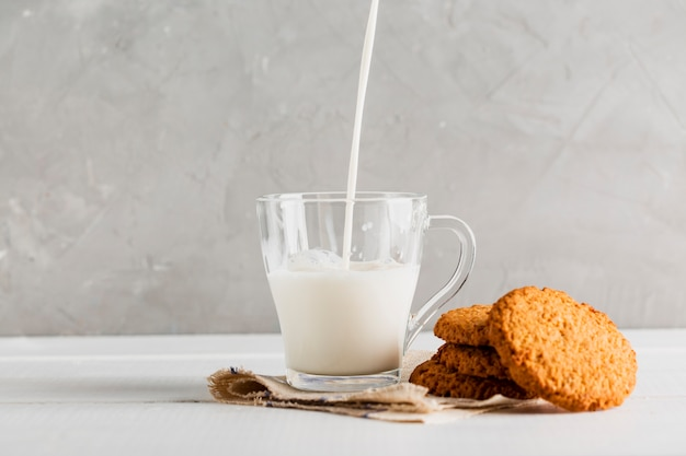 Milk pourred in glass with cookies